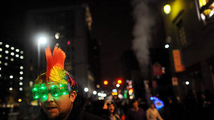 Damian Nunimaker of Jefferson Hills watches a band play Monday evening while wearing 2013 glasses during the city's First Night New Year's Eve festivities Downtown.