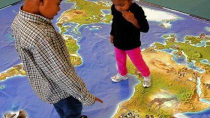 R.J. Bernard, 5, and his sister Rielle, 2, scrutinize an unusually large map of the world at the National Children's Museum.