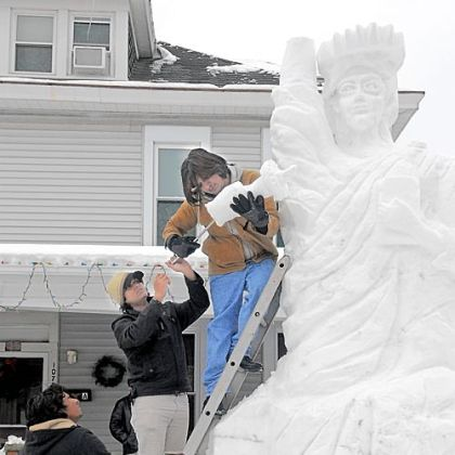 From top, Minhas Hameed, Umair Akhlas and Mohsin Hameed top off a 15-foot-tall Statue of Liberty made of snow in the front yard of their home Monday in the 1100 block of Fourth Avenue in Beaver. The families, who are Christians, are recent arrivals in the U.S., leaving their native Pakistan due to religious violence.