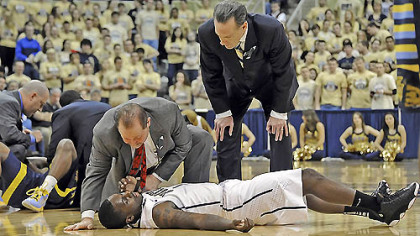Pitt's Tray Woodall is attended to by trainer Tony Salesi and head coach Jamie Dixon after colliding with Marquette's Derrick Wilson in the first half this afternoon at the Petersen Events Center. Woodall left the game with a concussion.