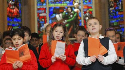 Leeann Parsi, Carlee Fettis and Mickey Gallagher, third-graders at St. Raphael School in Morningside, sing Friday at the memorial service honoring the 149th anniversary of Stephen Foster's death in the Temple of Memories at Allegheny Cemetery at Penn Avenue. The Stephen Foster Memorial Window is in the background.