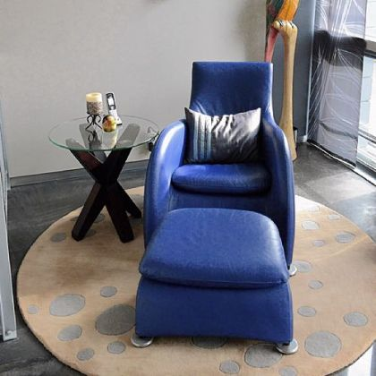 A blue chair and ottoman provide a small focal point in the living room.
