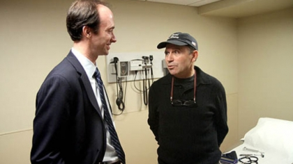 Toni Pais talks to UPMC neurosurgeon Mark Richardson during a checkup in February. Dr. Richardson has developed a treatment for Parkinson's in which surgery that once required a localized anesthetic can now be performed using a general anesthetic.