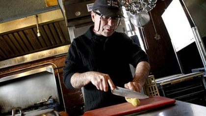 Toni Pais cuts into a squash in the kitchen at Cafe Zinho in Shadyside.