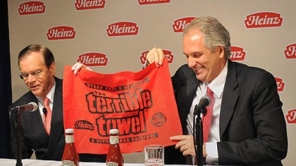 At a press conference today, Alex Behring, right, managing partner at 3G Capital was presented with a Heinz red Terrible Towel by William R. Johnson, chairman, president and CEO of Heinz.