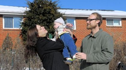 Heather Fowler and Aaron McGregor hold their son, Emmett McGregor, 12 months, in the backyard of their home.