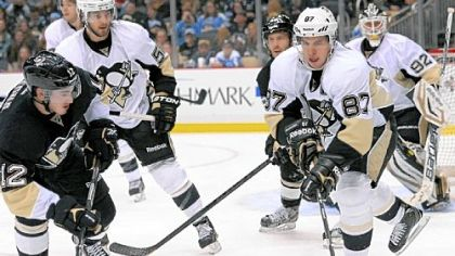 Jayson Megna, left, and Sidney Crosby, right, battle for the puck behind the net in the second period.