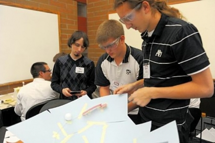Garrett Buyan, left, a judge at Technology Student Association competition, times Kevin Brenneman, center, 18, and Austin Hartman, 17, both of Ambridge Area Senior High School, as they demonstrate the device they created to keep a golf ball in motion for exactly 10 seconds.