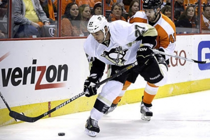 The Penguins' Craig Adams controls the puck in front of the Flyers' Andrej Meszaros.