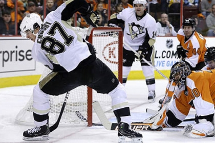 Philadelphia Flyers goalie Ilya Bryzgalov watches as the Penguins' Sidney Crosby (87) tries to control the puck during the first period.