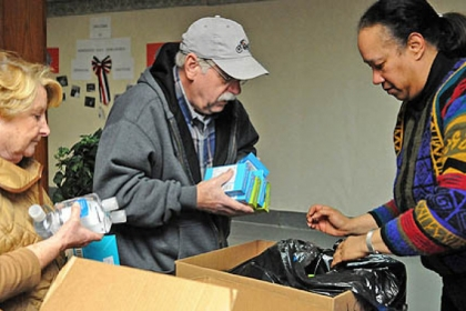 Ruth and Bob Sasser, left, from Upper St. Clair and Marva Williams from Penn Hills assemble care packages for military families in Pittsburgh at the Homewood AME Zion church in Homewood as part of the National Day of Service in honor of Rev. Martin Luther King, Jr.