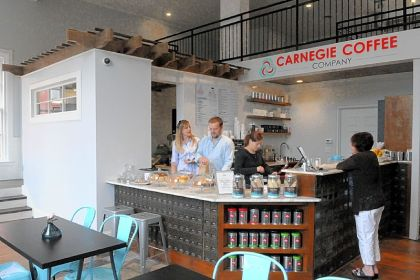 From left, owner Ashley Comer, general manager Matt Harkness and employee Amanda Dille wait on customer Marlayne Derenzo of Crafton at the newly opened Carnegie Coffee Co. in Carnegie. The new shop is inside a long-vacant former post office.