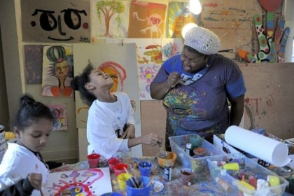 Trinity Reynolds, 6, left, paints while Tori Hammond, 8, center, laughs as artist Vanessa German sings at the Art House in Homewood.