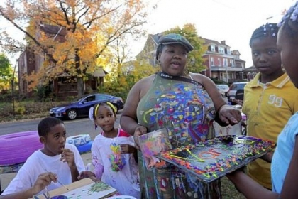 Sunny Littlejohn, 10, right, presents Vanessa German with a painting she made at the Art House.