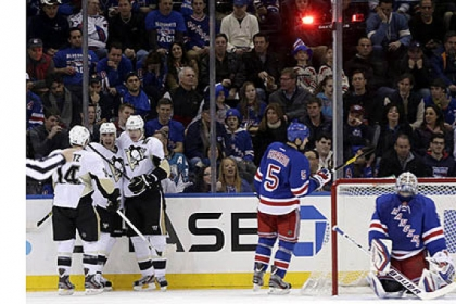 Rangers goalie Henrik Lundqvist, right, reacts while the Penguins' Pascal Dupuis, second from left, celebrates his goal with teammates Chris Kunitz, left, and Evgeni Malkin during the second period. The Rangers' Dan Girardi skates by.