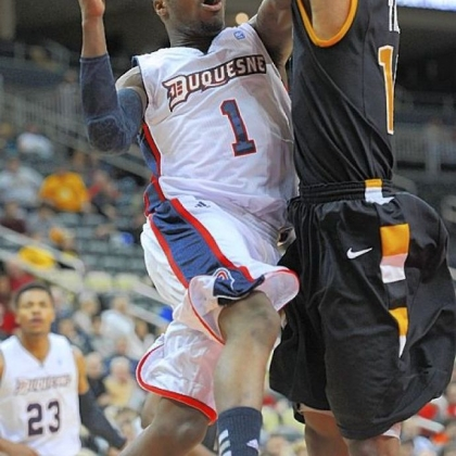 Duquesne&#039;s Derrick Colter drives to the basket against VCU&#039;s Darius Theus. Colter paced the Dukes with 15 points.