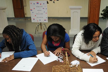 K'sandra Harding, 13, Jada Doleno, 13, Nila Andrews, 14, and Roman Burkes, 14, from the Melting Pot Ministries in the South Hills join in the National Day of Service in honor of Martin Luther King Jr. at the Homewood AME Zion church by writing letters to members of the military.