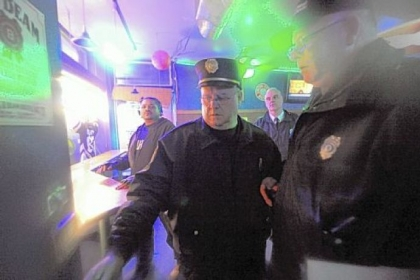 As part of the increased police presence on the South Side, fire Capt. James Flaherty, center, and police and building inspectors check inside Rumshakers on East Carson Friday night.