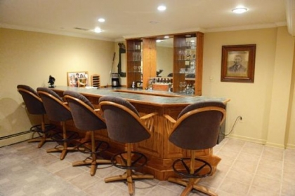 The basement has a wet bar with custom-made cabinetry, a full bath and a workout area.