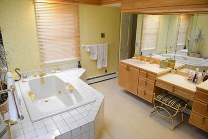 The master bathroom is roomy and light with double sinks and a makeup table combination.