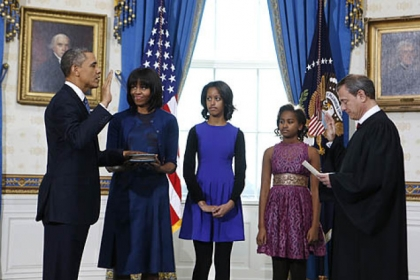 President Barack Obama, joined by First Lady Michelle Obama and daughters Malia and Sasha, is officially sworn in by Chief Justice John Roberts in the Blue Room of the White House.