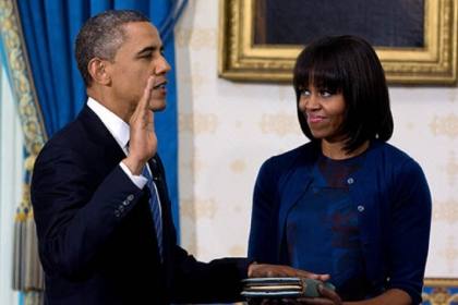 President Barack Obama is officially sworn in by Chief Justice John Roberts in the Blue Room of the White House as First Lady Michelle Obama holds the Robinson family Bible.