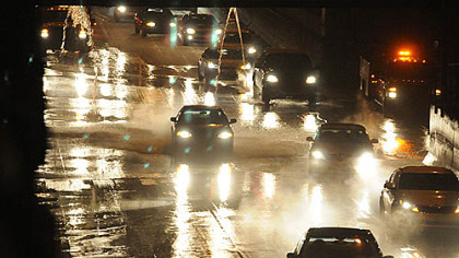"Cars and trucks in the ""bathtub"" area of the Parkway East dodge the water from the break."