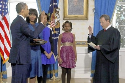 President Barack Obama is officially sworn in by Chief Justice John Roberts in the Blue Room of the White House on Sunday. Next to Mr. Obama are first lady Michelle Obama and daughters Malia and Sasha.