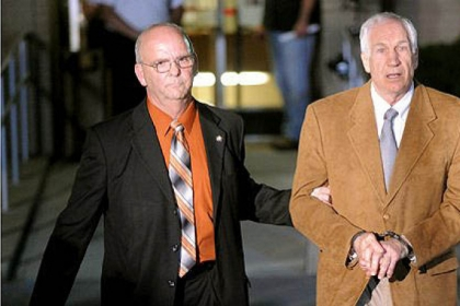 Jerry Sandusky is led in handcuffs by Centre County Sheriff Denny Nau after being found guilty June 22 on 45 counts of sexual abuse at the Centre County Courthouse in Bellefonte.
