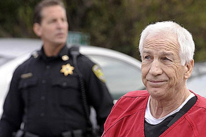 Former Penn State assistant football coach Jerry Sandusky in escorted into the Centre County Courthouse, for his sentencing on 45 counts of child sex abuse.