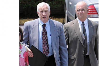 Jerry Sandusky leaves the Centre County Courthouse after the jury began deliberating his case. At right is Centre County Sheriff Denny Nau.