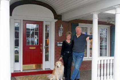 Jim and Mary Frances Miller on their front porch. Behind them is an original arched pediment found beneath the old portico during demolition.