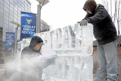 "Richard Bubin and his nephew, Jeff Bubin, of Ice Creations assemble a ""Great Day for Hockey"" ice sculpture outside the Consol Energy Center Wednesday."