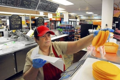 Becky Carl prepares a cheese order in the deli at Youngwood Corner Market. Ms. Carl starts before the store opens to prepare homemade soup and other hot foods.