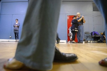Janine Hauck of Mt. Lebanon, at left, waits for instruction while Bea Herdon of the Hill District and Michael Young of Oakland dance together Jan. 13 during Tango 101 at the Wilkins School Community Center in Regent Square.
