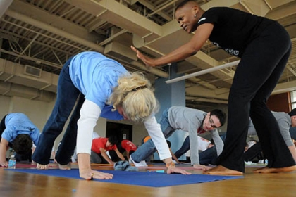 Volunteer students from the Shady Side Academy take Yoga instructions from Felicia Lane Savage (right) as a team-building exercise before making make rain barrels at the Kingsley Center in Pittsburgh's Larimer neighborhood as part of the school's Day of Service to celebrate Martin Luther King Day.