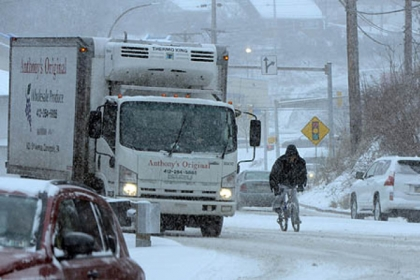 A cyclist rides through heavy snow and traffic on Banksville Road.