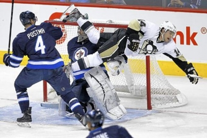 Winnipeg Jets' Paul Postma sends Pittsburgh Penguins' Chris Kunitz flying in front of Jets goaltender Ondrej Pavelec during the first period.