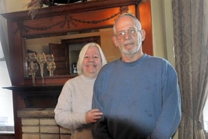 Cathy and George Lewis, owners of the Wigman house in Carrick, in front of one of the ornamental wooded mantels, this one in the dining room.