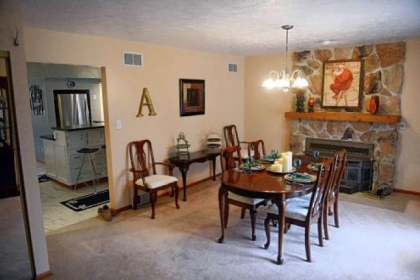 The dining room features a stone fireplace.