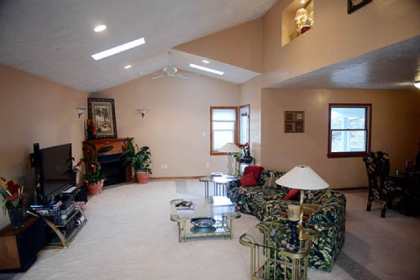 The living room with its slanted ceiling and three skylights is flooded with sunlight on most days.