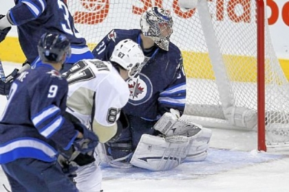 The Penguins&#039; Sidney Crosby scores his second goal against Winnipeg Jets&#039; goaltender Ondrej Pavelec during the first period in Winnipeg, Manitoba