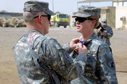 Col. Ricky Gibbs, an Army commander in Iraq, places a Purple Heart on the collar of Sgt. Jennifer Hunt, a civil affairs specialist, for wounds suffered in 2007 due to enemy contact during her deployment in support of Operation Iraqi Freedom.