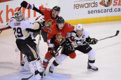 The Penguins' Sidney Crosby, right, ties up the Senators' Kyle Turris in front of Penguins goalie Marc-Andre Fleury as the Senators' Kaspars Daugavins, back, moves in.