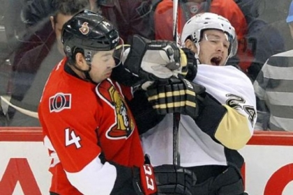 The Ottawa Senators' Chris Phillips, left, hits Penguins winger Matt Cooke in the second period.
