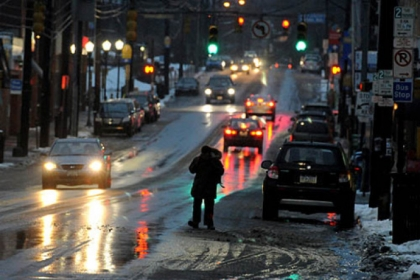 A man walks  along Murray Avenue in Squirrel Hill this morning while avoiding the slush and the slick sidewalk.