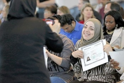 Miriam Bilaih shows off her U.S. citizen naturalization document Monday after a naturalization ceremony in Irving, Texas.