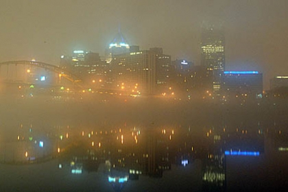 Pittsburgh's foggy skyline is reflected in the rivers before sunrise today.