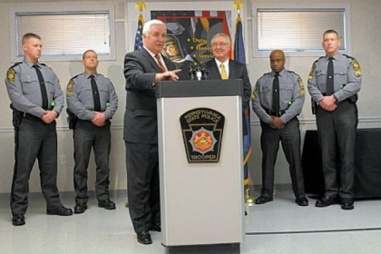 Gov. Tom Corbett, left at the podium Tuesday with Frank Noonan, commissioner of the state police, details his law enforcement budget and announces funding for three new classes of state police cadets. Behind the two are, at left, Troopers Greg Brown and Robert Klein and, at right, Cpls. Dave Watts and Chris Murray.