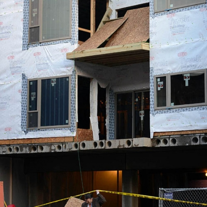 Police investigate a construction site where two workers fell three stories after the wooden landing they were on collapsed near the intersection of 49th and Harrison streets in Lawrenceville.
